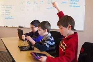 Kids in a classroom using tablet computers - a boy has his hand raised.