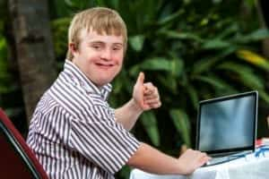 This is a picture of a handicapped student doing thumbs up sign next to a laptop.